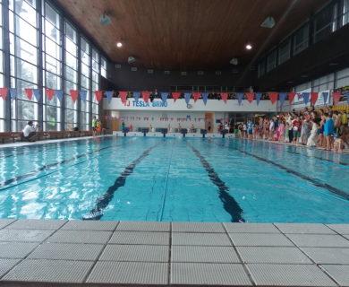 bazén bez lidí, určen pro plavání, lidé na vedlejší tribuně